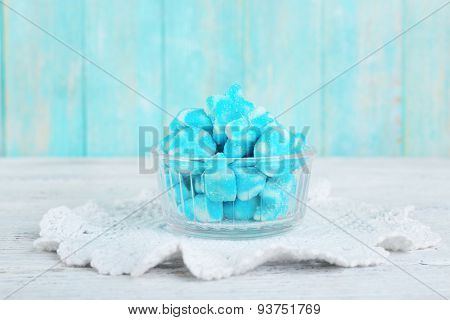 Blue candies in glass saucer on wooden background