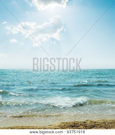 wave on sea and blue sky with clouds and sun