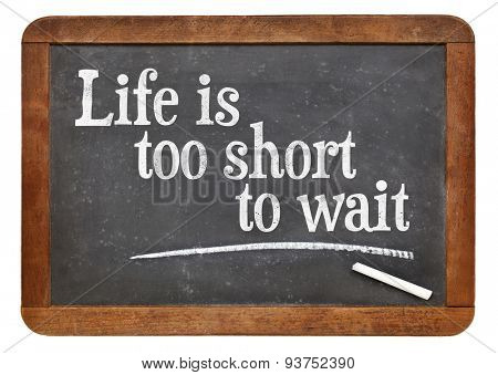 Life is too short to wait inspirational phrase - a text on an isolated  vintage slate blackboard