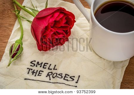 Smell the roses inspirational phrase - handwriting on a napkin with a red rose and coffee