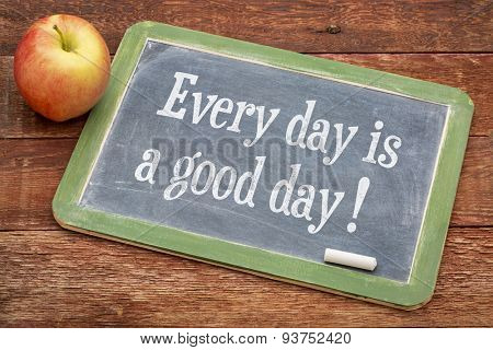 Every day is good day - positive words on a slate blackboard against red barn wood