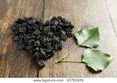 Raisins arranged in heart shape on wooden background