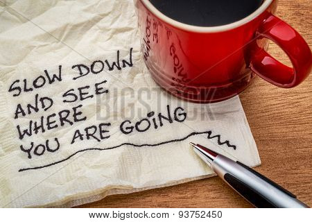 slow down and see where you are going - motivational reminder - handwriting on a napkin with a cup of coffee