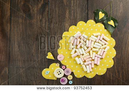 Marshmallow arranged in heart shape with buttons on table close up