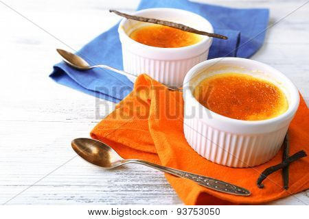 Creme brulee dessert  on napkin, on color wooden background