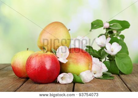 Fresh apples with apple blossom on wooden table, on nature background