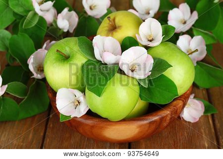 Fresh apples with apple blossom in bowl, on wooden table