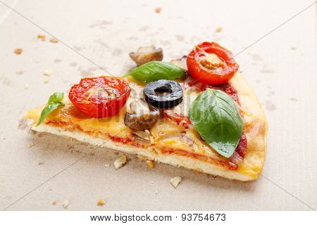 Slice of tasty pizza with vegetables and basil in cardboard box close up