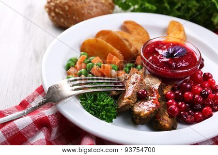 Beef with cranberry sauce, roasted potato slices, vegetables on plate, on color wooden background