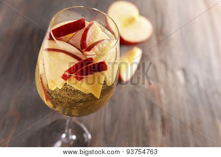 Glass of apple cider with fruits on wooden background