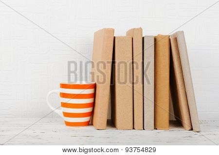 Books and cup on wooden shelf on wallpaper background