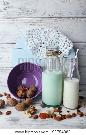 Milk in glassware and walnuts on background