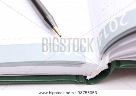 Brown Pen Lying On Open Organizer