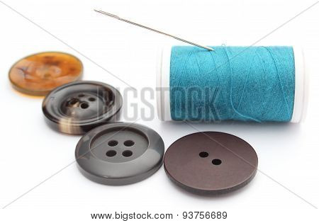 Sewing Buttons And Spool Of Thread On White Background