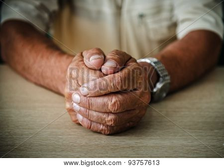 Wrinkled hands elderly man at table