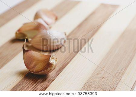 Raw garlic aloves on the cutting board