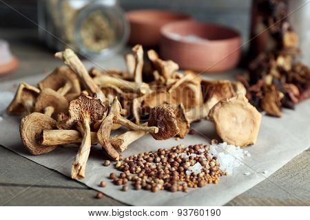 Dried mushrooms with spices on paper on wooden table, closeup