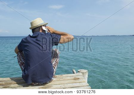 Man Talking On His Cell Phone At The Pier