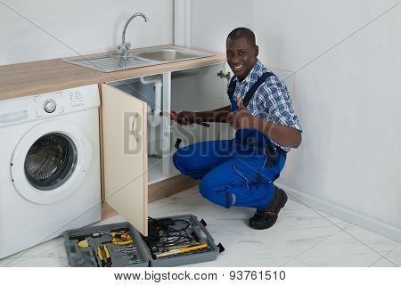 Male Plumber Fixing Sink In Kitchen