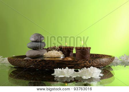 Spa still life with flowers and candlelight on green background
