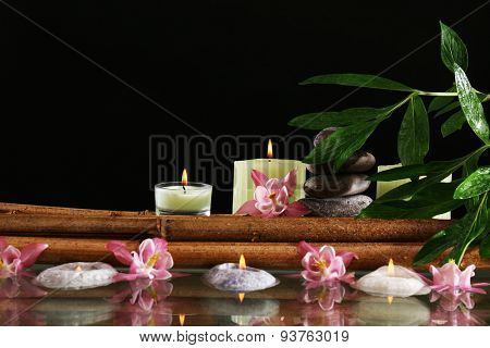 Spa still life with flowers and candlelight on black background