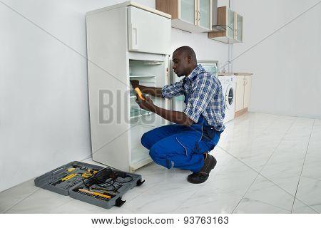 Young Repairman Repairing Refrigerator