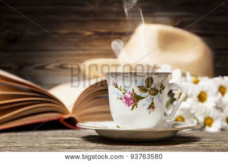 Coffee, daisies and a book on a wooden background