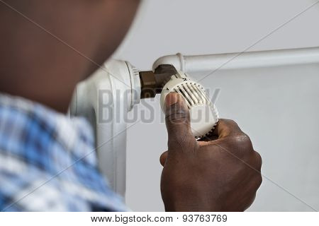 Person Hands Adjusting Thermostat Radiator