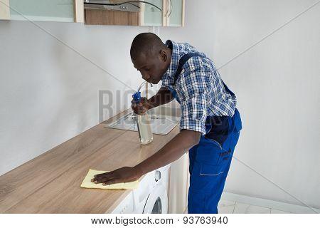 Man Cleaning Kitchen Worktop