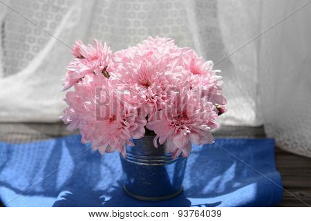 Beautiful chrysanthemums in vase on fabric background