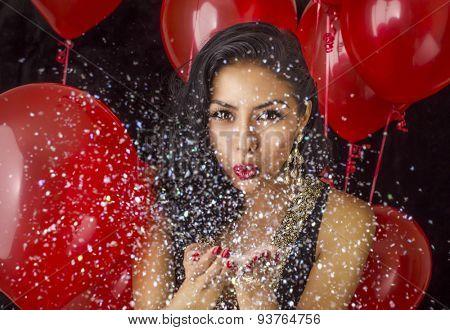 Beautiful young woman blowing confetti