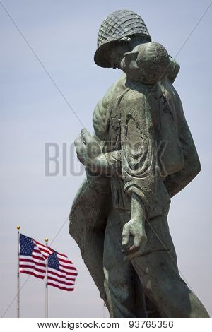 JERSEY CITY, NJ - MAY 26 2015: The Liberation Monument, a Holocaust memorial depicting a US soldier carrying a Nazi death camp survivor, with American Flags in the US Flag Plaza in Liberty State Park.