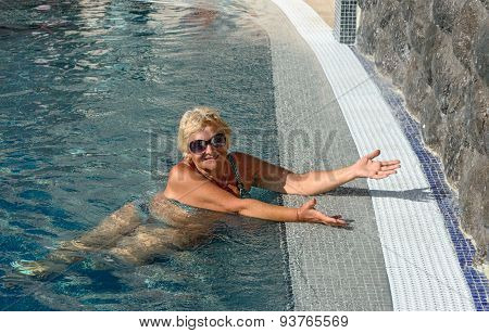 Aged Woman In Splashes On Water Of Pool Background.