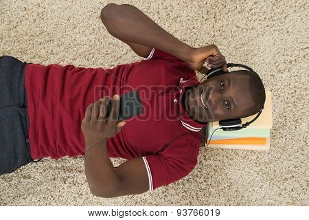 Man Lying On Stack Of Books Listening Music On Headphones