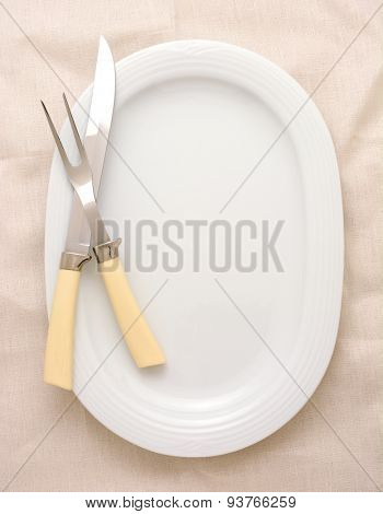A carving knife and fork on a platter, the platter is oval and white. The carving set has bone handles and the background surface is also off-white. High angle in vertical format.