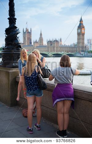 LONDON, UK - July 21, 2014:  London sunset. Big Ben, houses of Parliament and young tourists looking