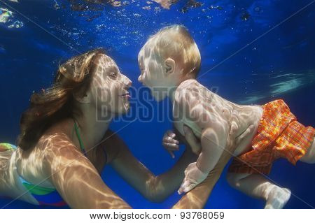 Little Child Swimming Underwater In Pool With Mother