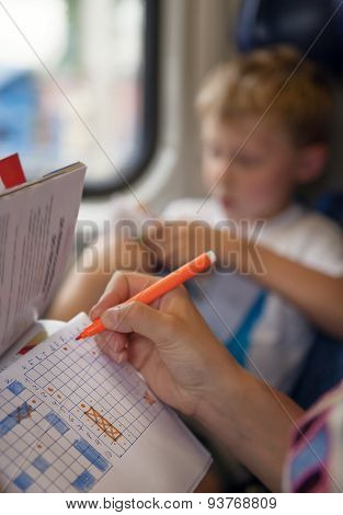 Son With Mother Playing A Sea Battle Game During Train Trip