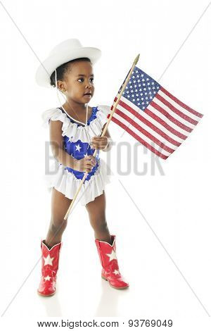 An adorable African American two year old prepared to march in a parade in her western majorette outfit of star-studded red, white and blue and carrying an American flag.  On a white background.