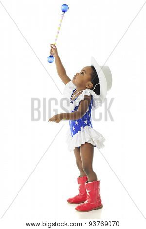 Profile of an adorable African American 2 year old wearing a western patriotic outfit and stretching high with her baton.