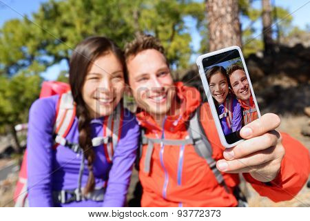 Selfie couple using smart phone camera taking photo hiking in nature with smartphone. Happy couple taking self-portrait picture using app. Man and woman having fun together. Focus on screen.