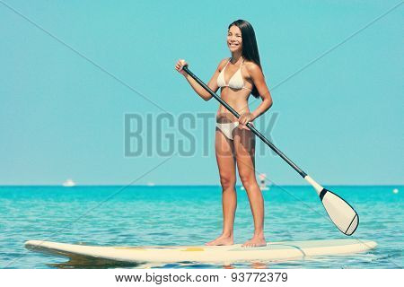 Stand up paddle board woman paddleboarding on SUP on Hawaii standing happy on paddleboard on in water. Young mixed race Asian Caucasian female model on Hawaiian beach on summer holidays vacation.