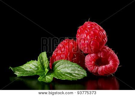 Ripe raspberry with mint leaves on a black background