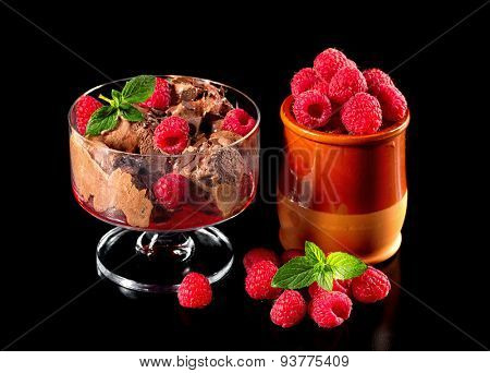 Chocolate ice cream with fresh raspberries isolated on a black background.
