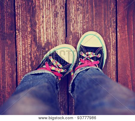a wide angle photo of a pair shoes with pink shoe laces on a vintage wooden background pointing one toe in toned with a retro vintage instagram effect app