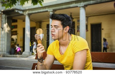 Attractive young man eating vanilla ice cream