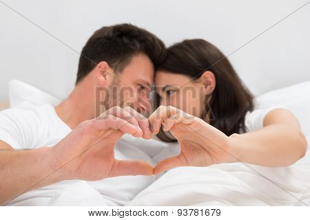 Couple Looking At Each Other Forming Heart Shape