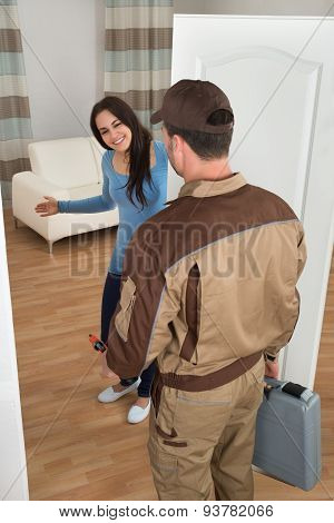 Happy Woman Welcoming Plumber At Home
