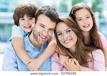 Family of four hugging each other