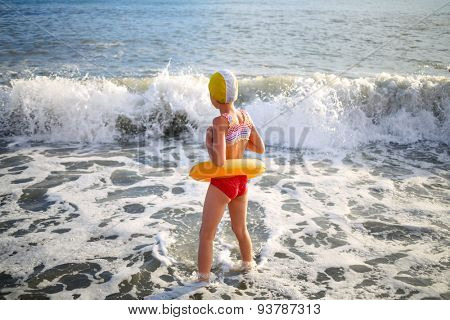 Girl in inflatable ring and a rubber cap in the sea waves